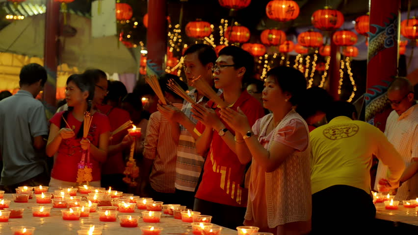 BANGKOK, THAILAND  - FEBRUARY 9, 2013: Thai-Chinese family praying for a prosperous new year on the eve of Chinese New Year in Chinatown, Bangkok, Thailand. They are praying at Wat Mangkon Kamalawat.