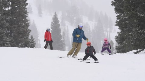 Parents and their children ski to camera together on snowy winter day at Alta Ski Area, Utah.