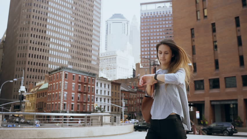 Young beautiful businesswoman walking in financial district in New York, America, looking on watch. Slow motion.