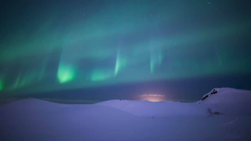Colorful aurora borealis sprites dancing over deep snow winter lanscape Iceland