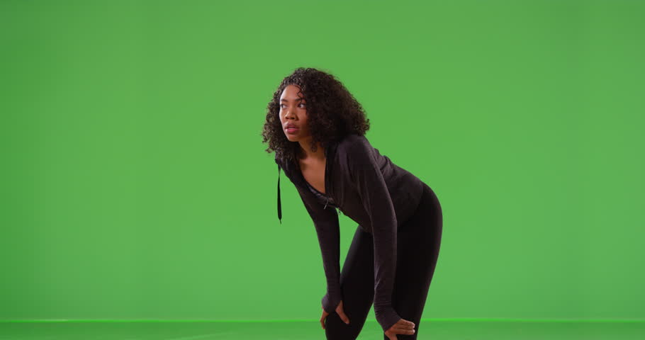 Black woman runner stretching and resting during workout run on greenscreen. Young African American jogger with hands on knees taking break from fitness on green screen. 4k | Shutterstock HD Video #33810160