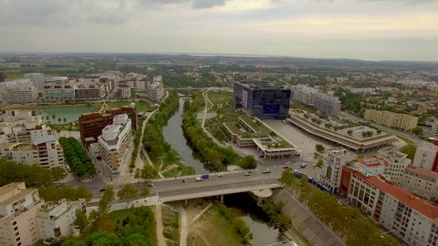 Aerial shot circling slowly over the River Lez in urban Montpellier