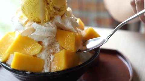 Mango shaved ice, also known as Bingsu Korean dessert, served with sticky rice, whipped cream and mango ice cream on the table.