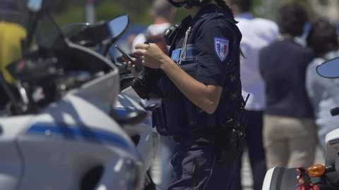 Female police officer standing next to motorbike, checking mobile phone on duty