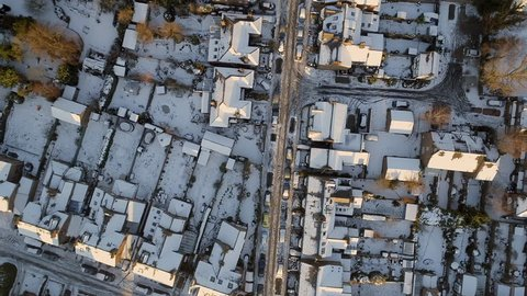Bird's Eye View of Houses in England on a Snowy Morning With Rooftops Covered in Snow and Cars Driving Along the Icy Roads