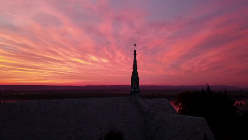 Drone shot of silhouetted monastery chapel and steeple rises to reveal the Mississippi River just before dawn. Sky is vibrant with pre-dawn colors, oranges, reds, purples, blues.