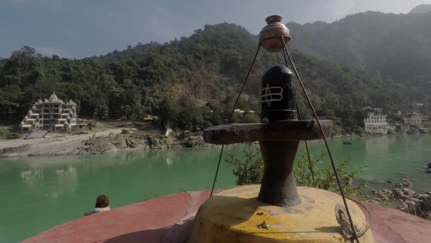 Shiva Lingam rotating tracking shot with Ganges River, hills and mountains in background. Rishikesh, India. 2X slow motion. Mid shot.