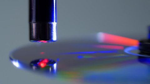 The red laser beam slides over the surface of the compact disk and reads the data on light background. Colorful reflections on the disc. Macro. Closeup. Shallow depth of field