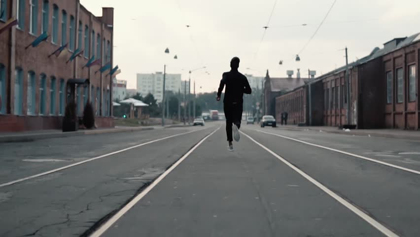Man running along an old city district street. Back view. On the way to success and reaching goals. Contrast shot. #33920149