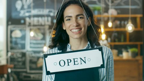 Beautiful Young Cafe Owner Flipping Storefront Sign From Close to Open and Welcoming New Customers into Her Modern Looking Stylish Coffee Shop. Slow Motion. Shot on RED EPIC-W 8K Helium Cinema Camera.