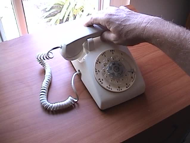 a person picks up the receiver and dials a fictitious phone number on an old rotary telephone with sound