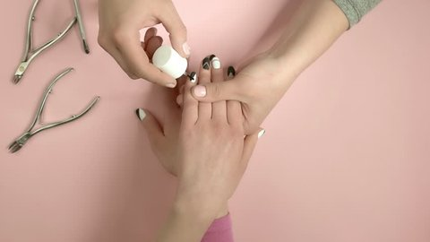 Manicurist applying oil on female nails. Nail beautician processing client nails and cuticle with oil on pink beauty salon background, top view. Hands and nails care.