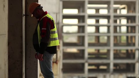 Worker knocks his head against the wall. Stressed builder in hard hat stands on construction site and knocks his head against the concrete wall, self-condemnation and self-torture