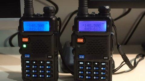 Two black handled portable walkie- talkie radio transmitter working and flashing in the dark