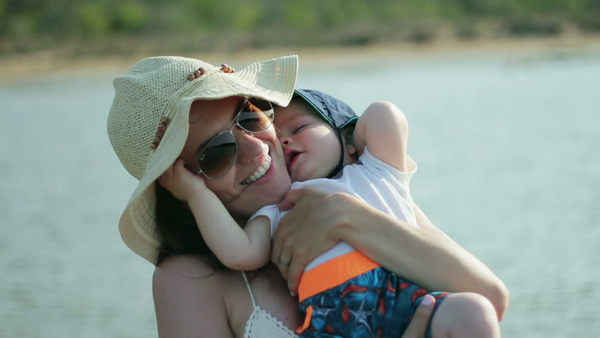 Portrait of happy loving mother hugging her baby on the beach #34057789