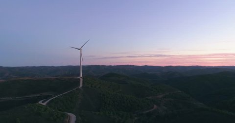 Aerial wind farm turbine generators at dusk. Clean renewable energy power production concept. Algarve countryside. Portugal.
