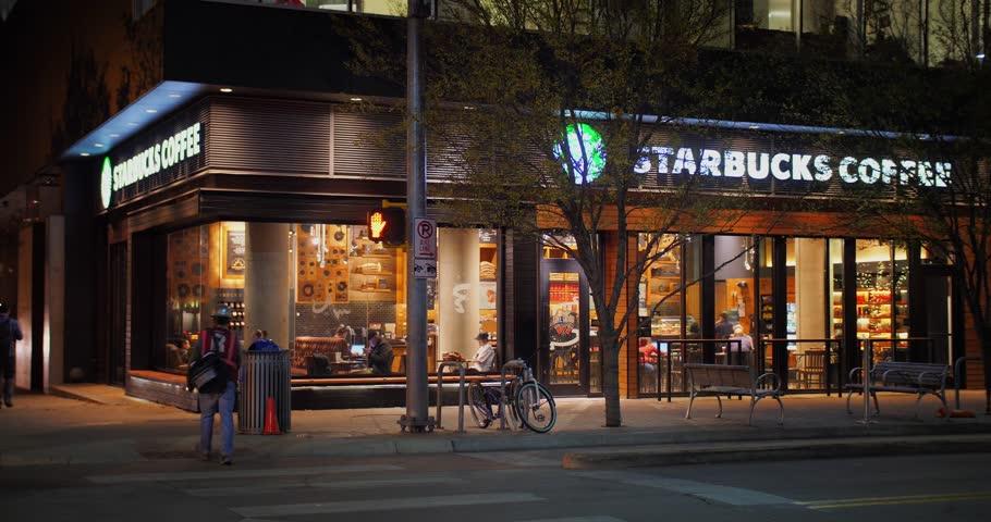 AUSTIN, TX - Circa December, 2017 - A nighttime establishing shot of a Starbucks Coffee Shop on Lavaca Street in downtown Austin, Texas.  Day/night matching available.