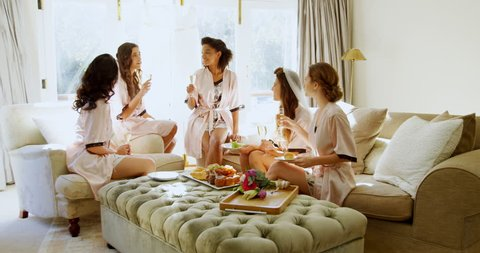 Seating on sofa bridesmaids in nightdress toasting a glass of champagne 4K