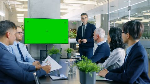 Businessman Gives Report/ Presentation to His Business Colleagues, Pointing at Green Chroma Key Screen Wall TV. Shot on RED EPIC-W 8K Helium Cinema Camera.