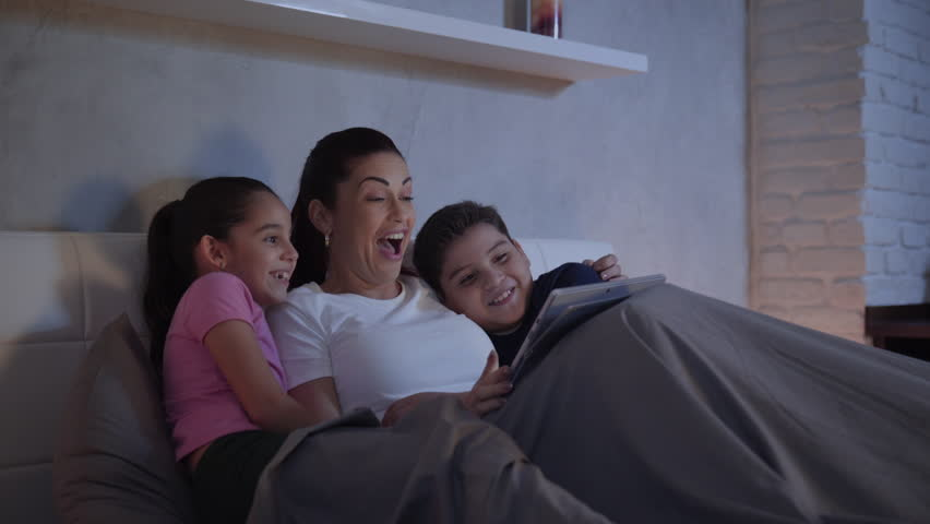 A mother and her children in bed enjoy a streaming movie in their tablet during a weekend night. A single caucasian woman and her kids having fun spending quality time together.  | Shutterstock HD Video #34086679