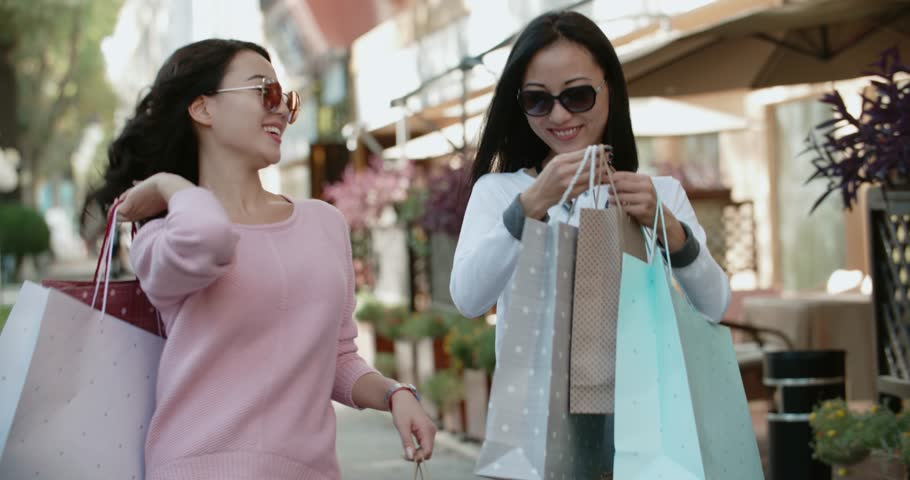 Two beautiful Asian girls have fun walking down the street with their purchases after shopping , Steadicam shot | Shutterstock HD Video #34089919
