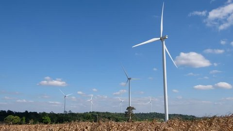 A turbine having a large vaned wheel rotated by the wind to generate electricity and Blue sky background with white clouds.