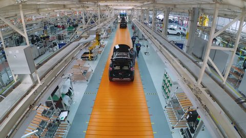 BELARUS, BORISOV - OCTOBER 19, 2017: Automobile plant, modern production of cars, car body assembly process, workers serve cars, automated production line. Timelapse, October 19 in Borisov, Belarus.