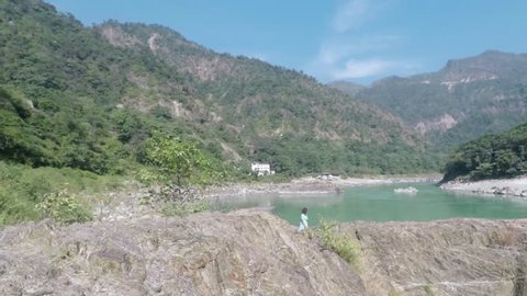Caucasian Hindu woman walks up steps to Shiva Lingam, in Rishikesh, India. Hills, river and ashrams in background. Smooth tracking. Wide. 2X slow motion.