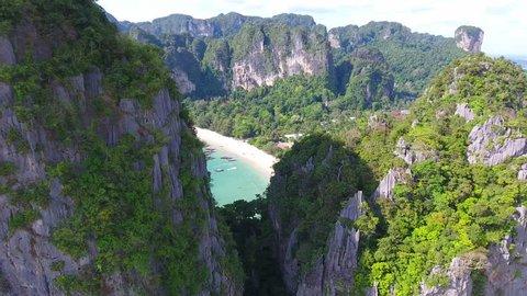 Cinematic Ariel Shots of Railay Beach Krabi Thailand going through cliffs revealing beach.