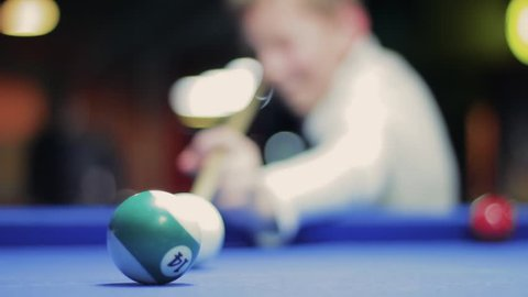 American billiard, nine-ball pool. Boy playing billiard, snooker. Player shooting, hitting the ball. Kid in white likes play on blue table