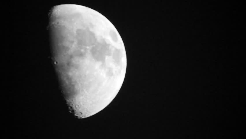 Close-up of half moon moving over the night sky.