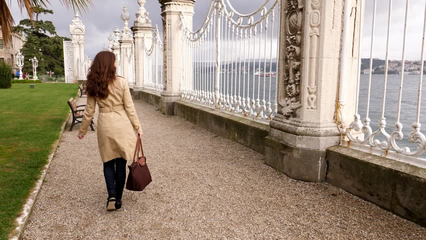 Tourist woman walk along fence and sit on bench with Bosphorus strait view, Dolmabahce Palace embankment park. POV camera follow lady and show waterway panorama seen from garden | Shutterstock HD Video #34116979