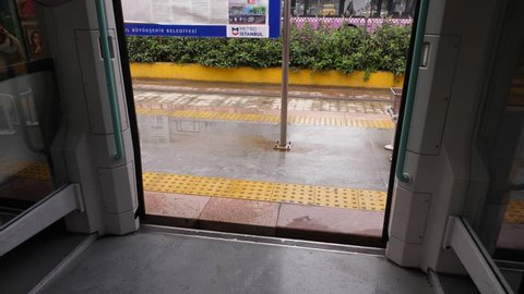 ISTANBUL - NOVEMBER 04, 2017: POV look at wet platform from inside tram vehicle, unidentified passengers walk by outside. Tramway standing still, wet pavement after rain. Empty passage and doorway