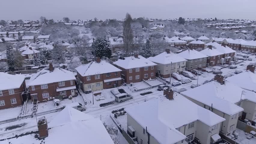 Panning aerial shot of snow covered street in the UK.