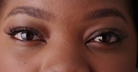 Close up of black female's beautiful eyes looking at camera on green screen. Close-up of eyes with gorgeous, long lashes blinking on greenscreen to be keyed or composited.