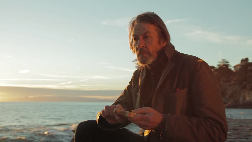 Old man carving wood sculptures at seaside during sunset | Shutterstock HD Video #34152409
