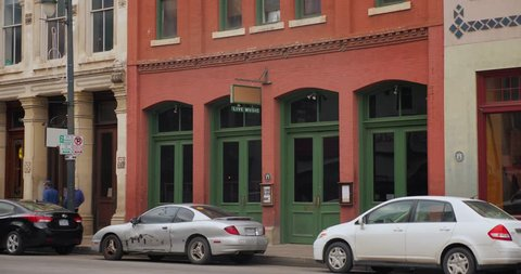 A daytime establishing shot of bars and restaurants on E 6th Street in the historic tourist district of Austin, Texas. Day/night matching available.