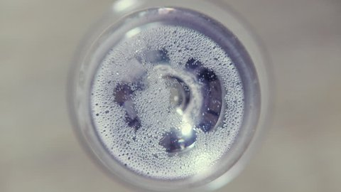 Round view of a sparkling wine glass from the top with lots of tiny bubbles