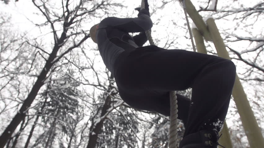 Slow Motion Of Young Muscular Sportsman Climbing Up The Rope Outdoors