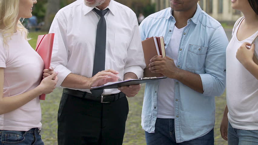 Senior coach talking to students, discussing education plan or test results | Shutterstock HD Video #34217389