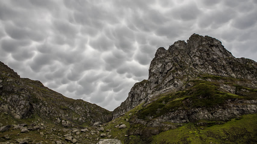 Mammatus storm clouds. Summer highland landscape. Mountain green peaks