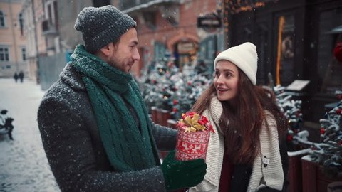 Beautiful young couple walking city man gives a gift to a woman christmas love happiness people person xmas year fair girl lights town attractive holding lifestyle santa fun joy holiday