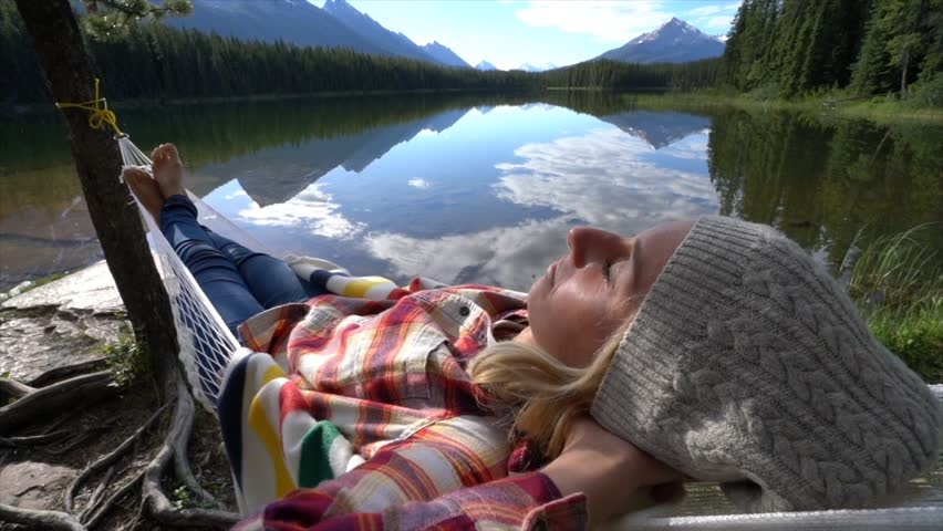 Shot of a young woman relaxing on hammock bu the mountain lake in Jasper national park, Alberta, Canada People travel relaxation concept Slow motion #34249819