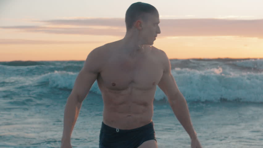 Close up of handsome mscular man standing tired at sea after swim