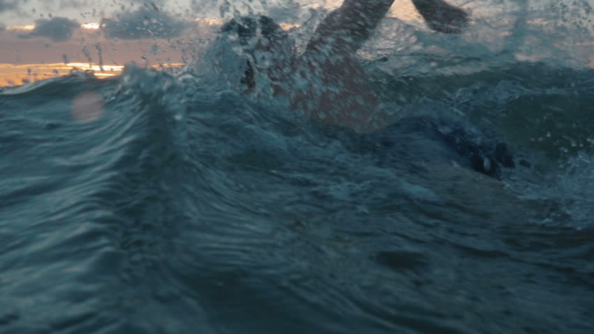 slow motion of professional swimmer swimming crawl outdoor on sunset, front view