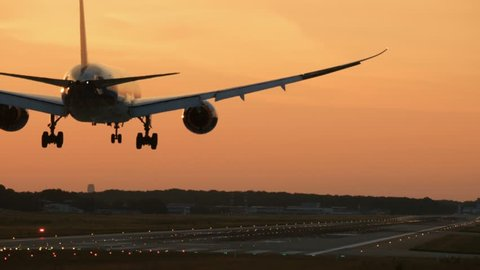Rear view of widebody twin engine airplane landing in the early morning. Picturesque sunset at the background,