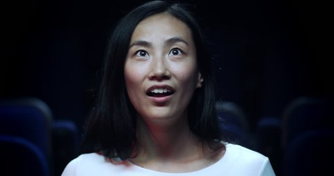 Close up, slow motion reaction shot of a Chinese girl reacting in awe in the movie theatre.