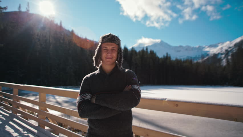 Closeup Winter Portrait of a Self-Confident Young Man in Ear Flapped Fur Hat Looking at Camera with Beautiful Mountains and Snow at Background with Sun Lense Flare
