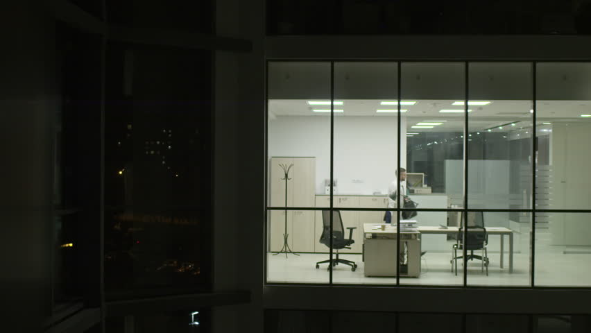 View from outside of modern glass office of businessman taking briefcase and coat, leaving workplace at night and turning off the light