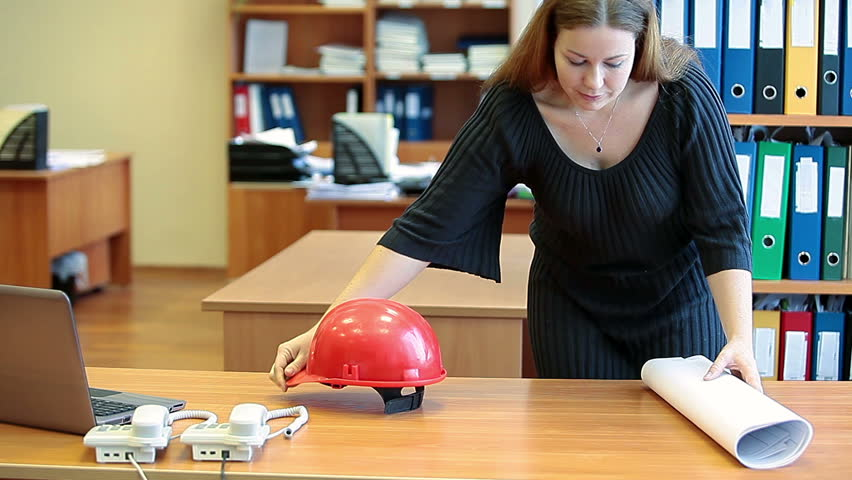 HD video of beauty architect girl at work. Standing behind a table with hardhat and blueprints